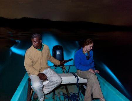 Clifford steers the boat through the bioluminescent lagoon as Kelci is awestruck by the brilliant blue glow of the boat wake