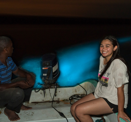 Sarah poses in front of the spectacular, glowing boat wake as Clifford makes a slow turn through the bioluminescent lagoon.